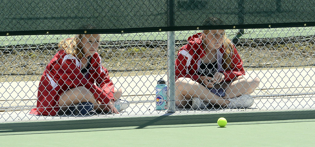 . Loveland\'s No. 3 doubles team Rebecca Emme (left) and Allison Westbrook peek through the fence to watch teammate Ava McQuade play for the 4A Region 4 title at No. 3 singles Friday at North Lake Park. (Mike Brohard/Loveland Reporter-Herald)
