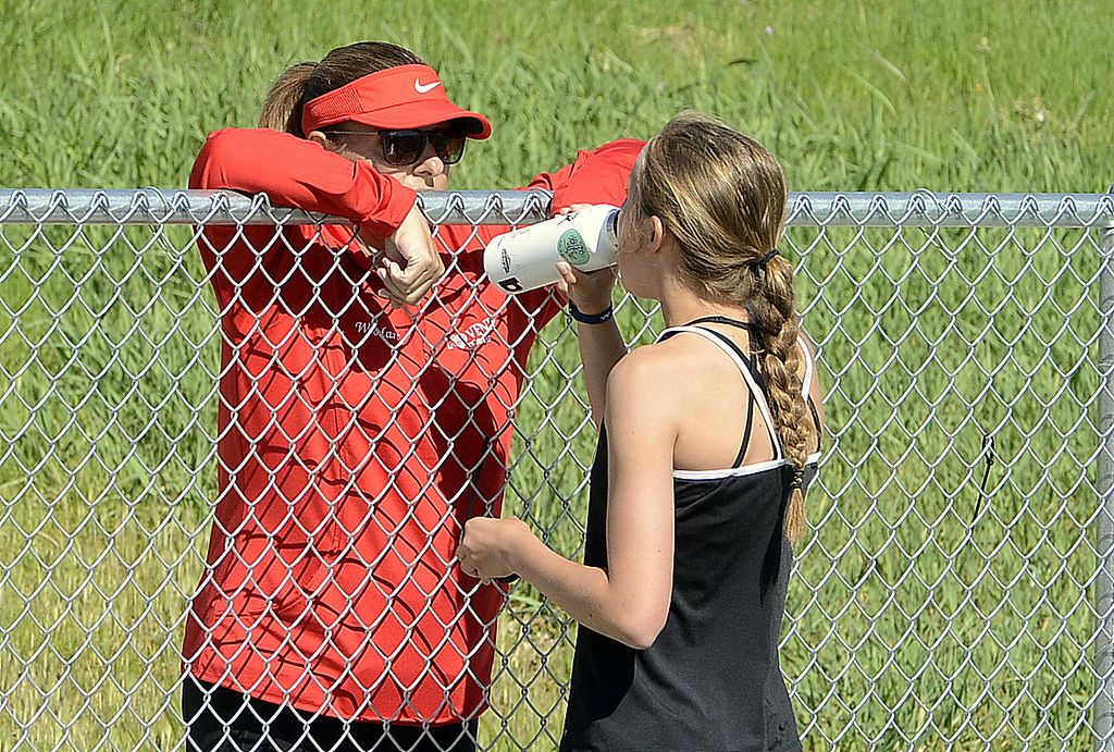 . Loveland coach Heidi Abrahamson looks over the fence to chat with No. 2 singles player Alix Huhta on Friday at the 4A Region 4 tournament at North Lake Park. (Mike Brohard/Loveland Reporter-Herald)