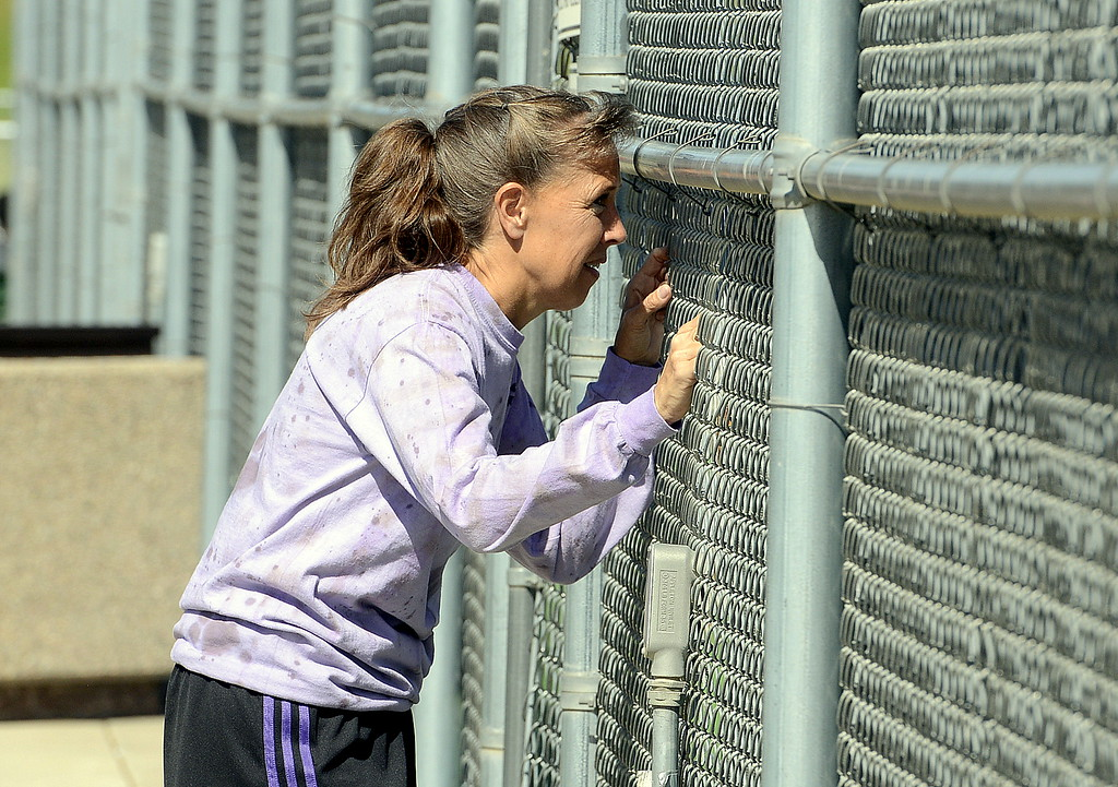 . Mountain View coach Patti Lang stands at the fence and talks to one of her players Friday during the 4A Region 4 tournament at North Lake Park. (Mike Brohard/Loveland Reporter-Herald)