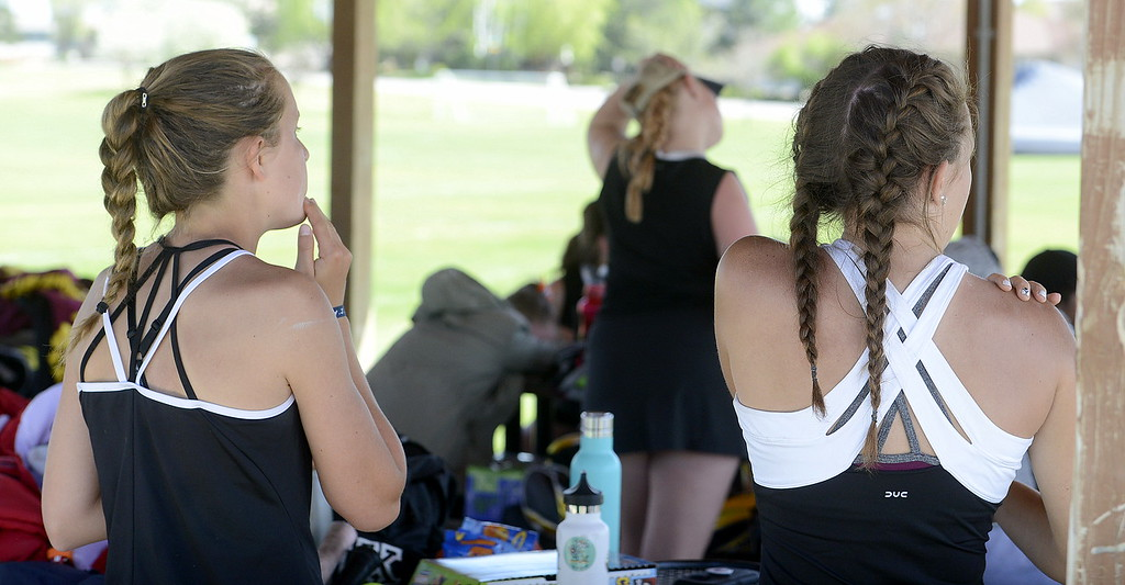 . Loveland\'s Alix Huhta (left) and Kira Badberg apply sunscreen as they await their return to the court Friday during the 4A Region 4 tournament at North Lake Park. (Mike Brohard/Loveland Reporter-Herald)
