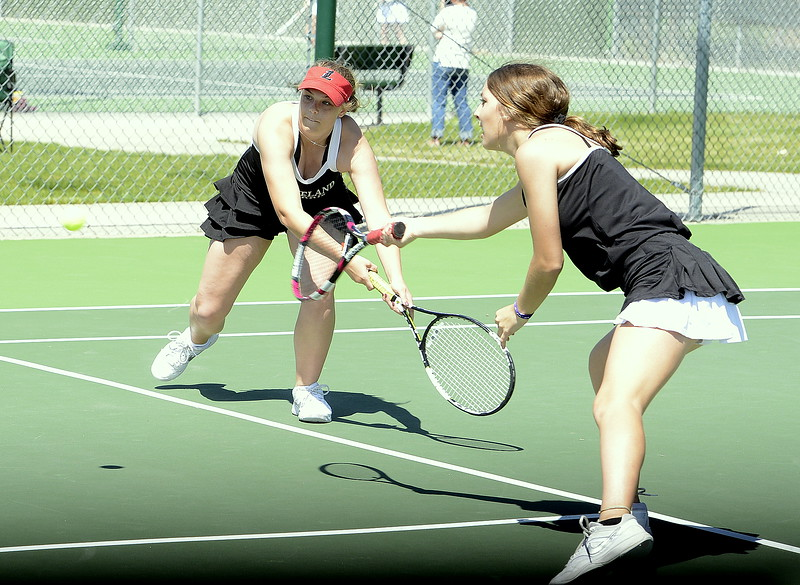 Loveland No. 1 doubles players Emily Eggerling (left) and Heather Price both go for a shot Friday during the 4A Region 4 tournament at North Lake Park. (Mike Brohard/Loveland Reporter-Herald)