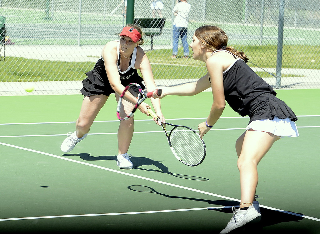 . Loveland No. 1 doubles players Emily Eggerling (left) and Heather Price both go for a shot Friday during the 4A Region 4 tournament at North Lake Park. (Mike Brohard/Loveland Reporter-Herald)