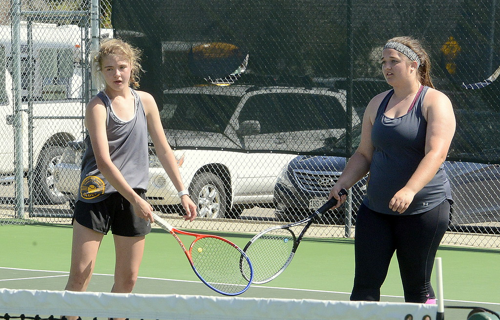 . Thompson Valley No. 2 doubles partners Emily Black (left) and Kaitlin Morris touch racquets after winning a point in the championship match Friday at the 4A Region 4 tournament at North Lake Park. They dropped a 6-1, 6-3 decision to Windsor. (Mike Brohard/Loveland Reporter-Herald)