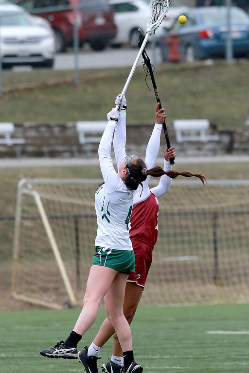 . Fitchburg High School girls Lacrosse played Oakmont Regional High School on Tuesday afternoon in Ashburnham, April 9, 2019. ORHS\'s Audrey Dolan and FHS\'s Diandra Boddie fight for control of the ball on a face-off. SENTINEL & ENTERPRISE/JOHN LOVE
