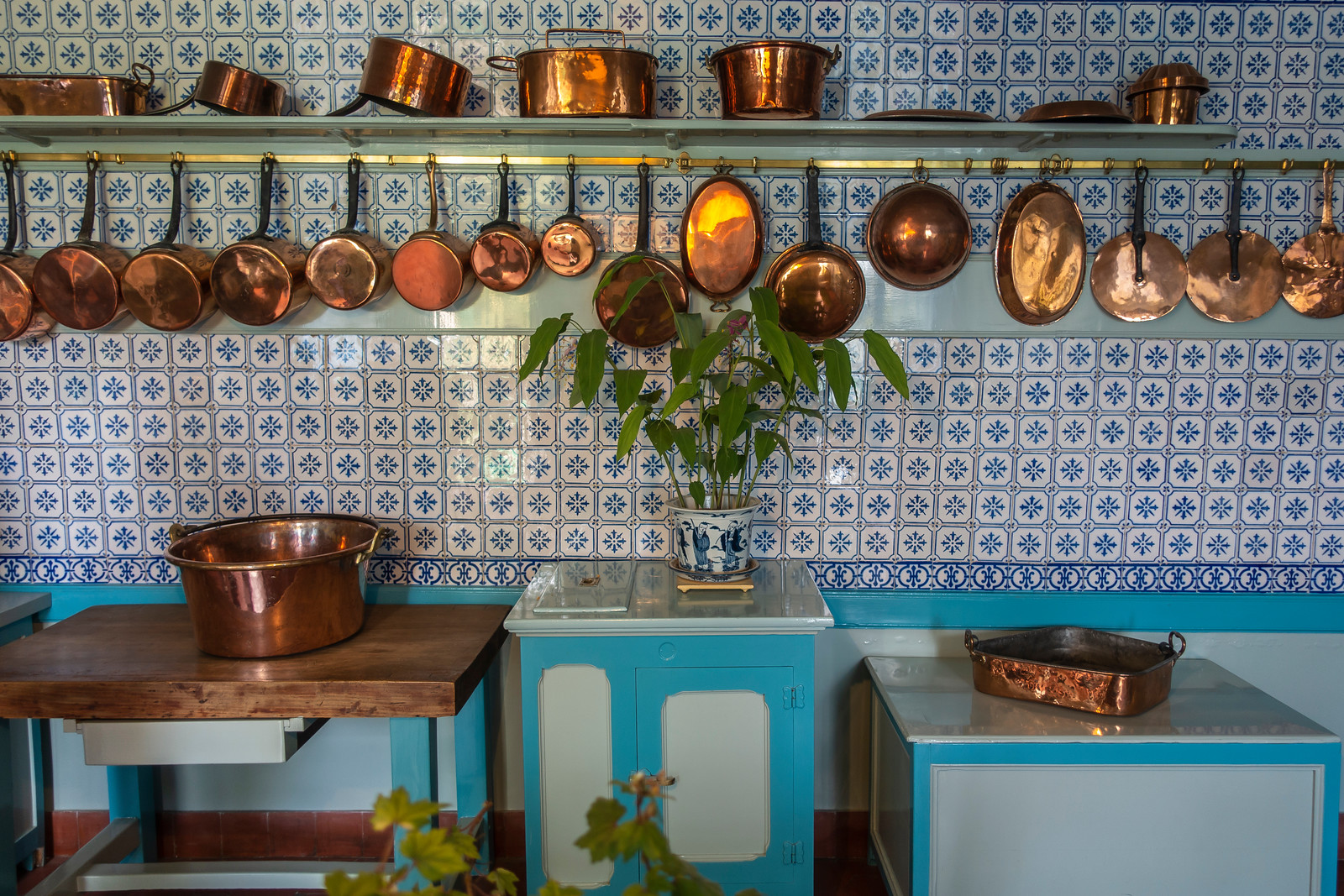 Monet's kitchen - copper pots of all shapes and sizes are are hanging on the walls decorated with blue Rouen tiles