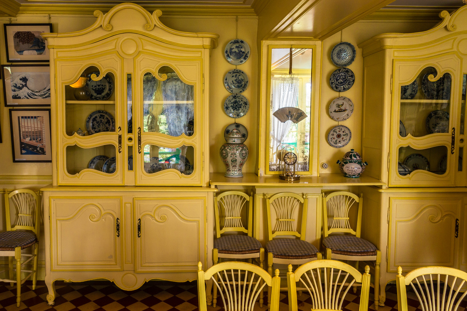 Monet's fabulous yellow kitchen featuring detailed yellow cabinets, yellow chairs and china pieces hanging on the walls.