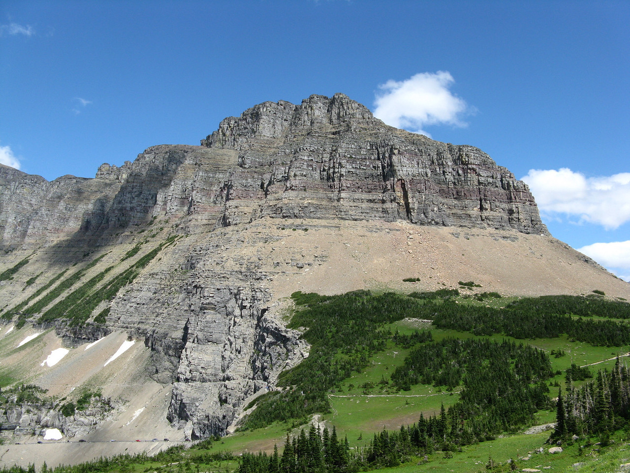 Looking north from just west of Logan Pass, the ridge that stretches for miles in a northward direction is called the Garden Wall.  The road is a thin line near the bottom left side of the image.  The Highline Trail is the white line in the green meadow in the lower right quadrant of the picture.