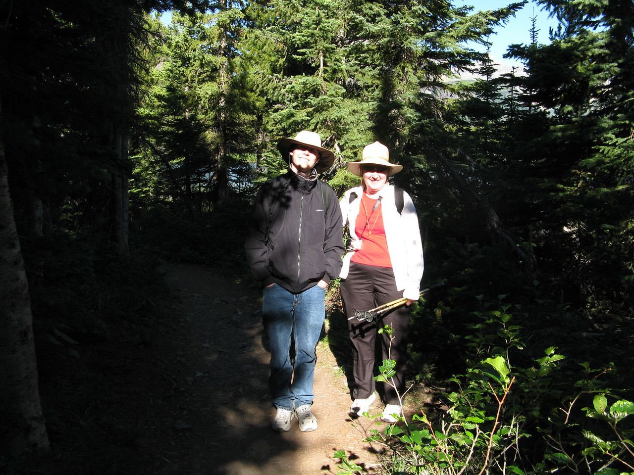Early mornig sun on Kevin and Mary.  We hiked on level trail in evergreen forest around Swiftcurrent Lake on the south shore.