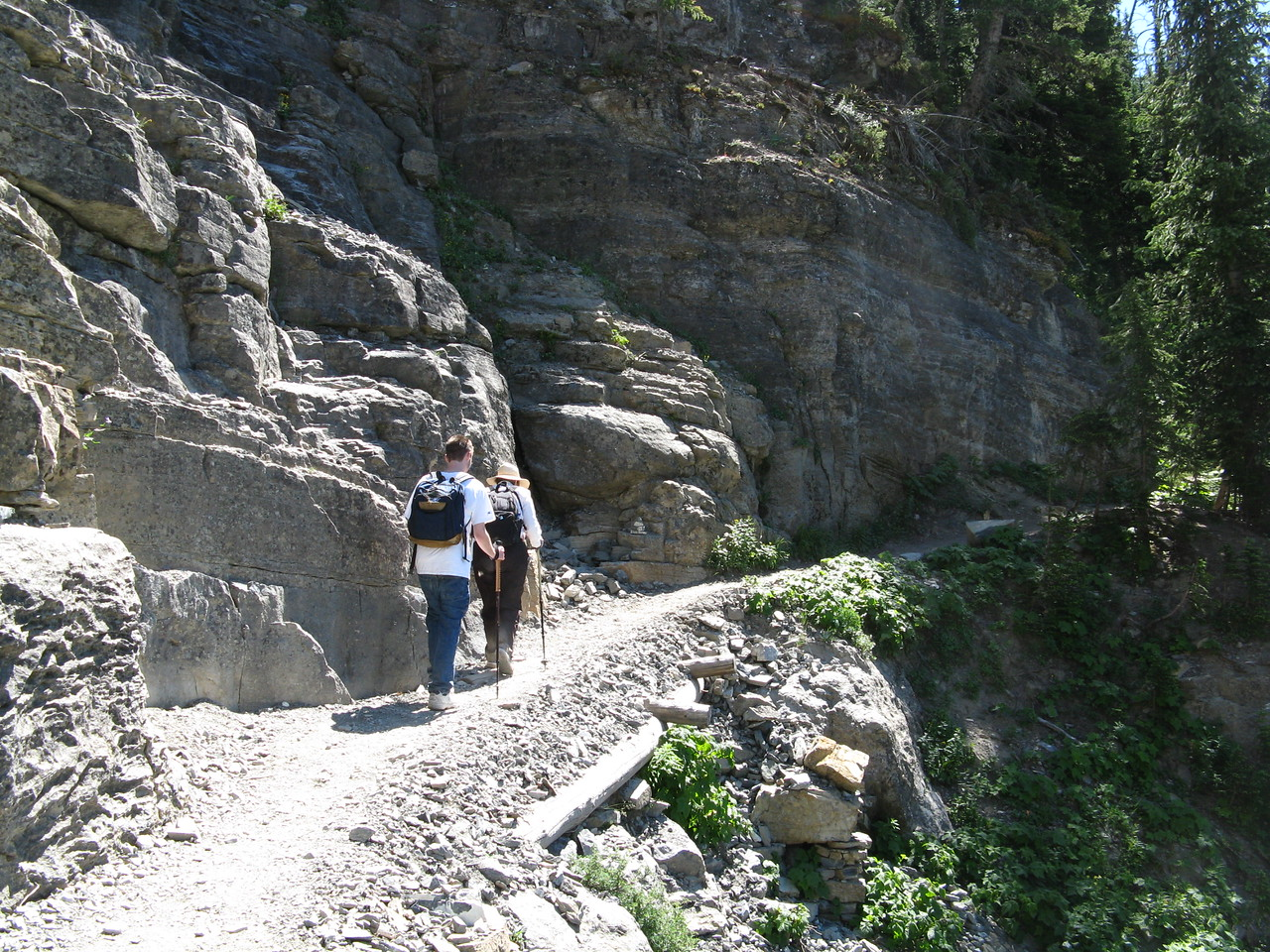The trail climbs away from the rock ledge.