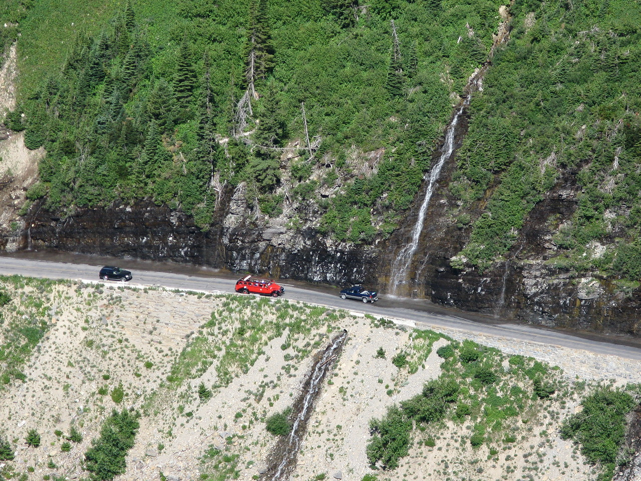 This short section of the Going-to-the-Sun Road is called the Weeping Wall.  A waterfall cascades down onto the roadway.  Near the center of the picture is a red jammer tour bus.  It has a canvas roof, which appears to be in the retracted position.  The tourists are going to get wet under the falls.