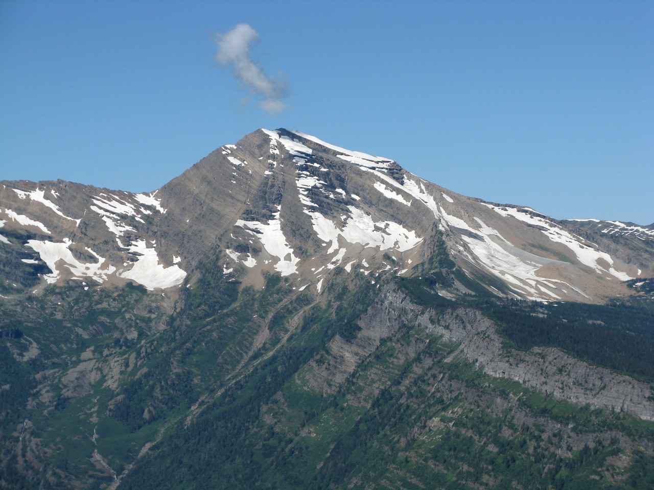 A closeup of Heavens Peak.  The white collection is a cloud, not a plume of steam.   The mountains in Glacier NP appeared to be sedimentary rock, which implies the rocks were once ocean floors that were lifted up by tremendous geological forces.