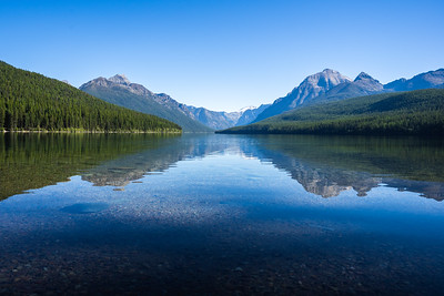 Calm Lake Bowman with a Reflection of Mountains in the Background in Northern Glacier National Park