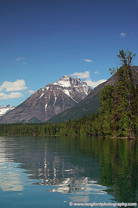 Mountains are reflected in Lake McDonald in this scene.  This was shot from behind Lake McDonald Lodge.