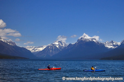 Kayakers take in the beautiful mountain scenery of Lake McDonald.  This shot was taken near Apgar Village.