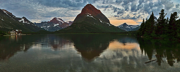 Panoramic image of Swiftcurrent Lake, with Many Glacier lodge in the distance. This was shot very early in the morning as the sun was rising behind me.  The early morning light is just starting to hit the mountains in front of me.