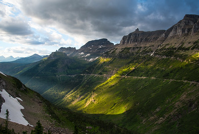 The day's last light sweeps across the valley floor with Going to the Sun Road bisecting the dramatic cliffs of Glacier National Park in the background