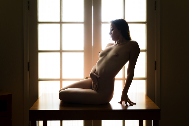 Middle aged caucasian woman poses nude on a table while backlit
