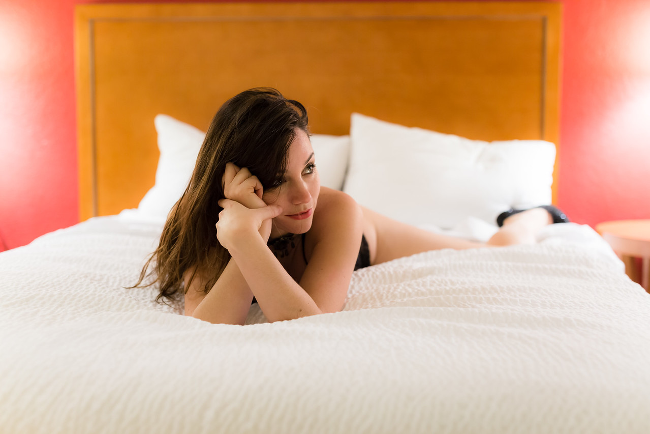 Middle aged caucasian woman dressed in lingerie poses on a bed in a bedroom