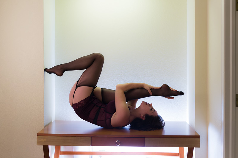 Middle aged caucasian woman dressed in lingerie poses on a table against a square alcove