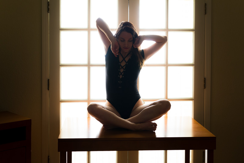 Middle aged caucasian woman in black leotard poses on a table while backlit