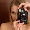 Blonde caucasian woman in underwear plays with a retro film camera
