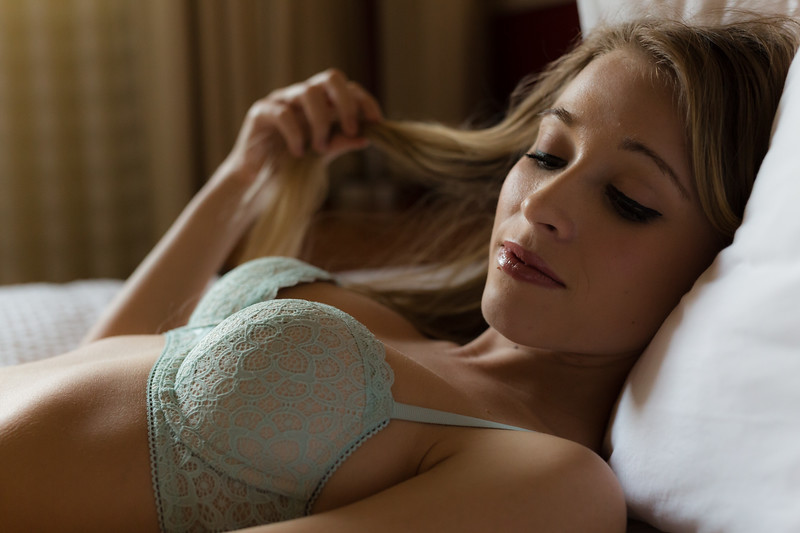 Blonde caucasian woman in blue lingerie poses on a bed in natural light