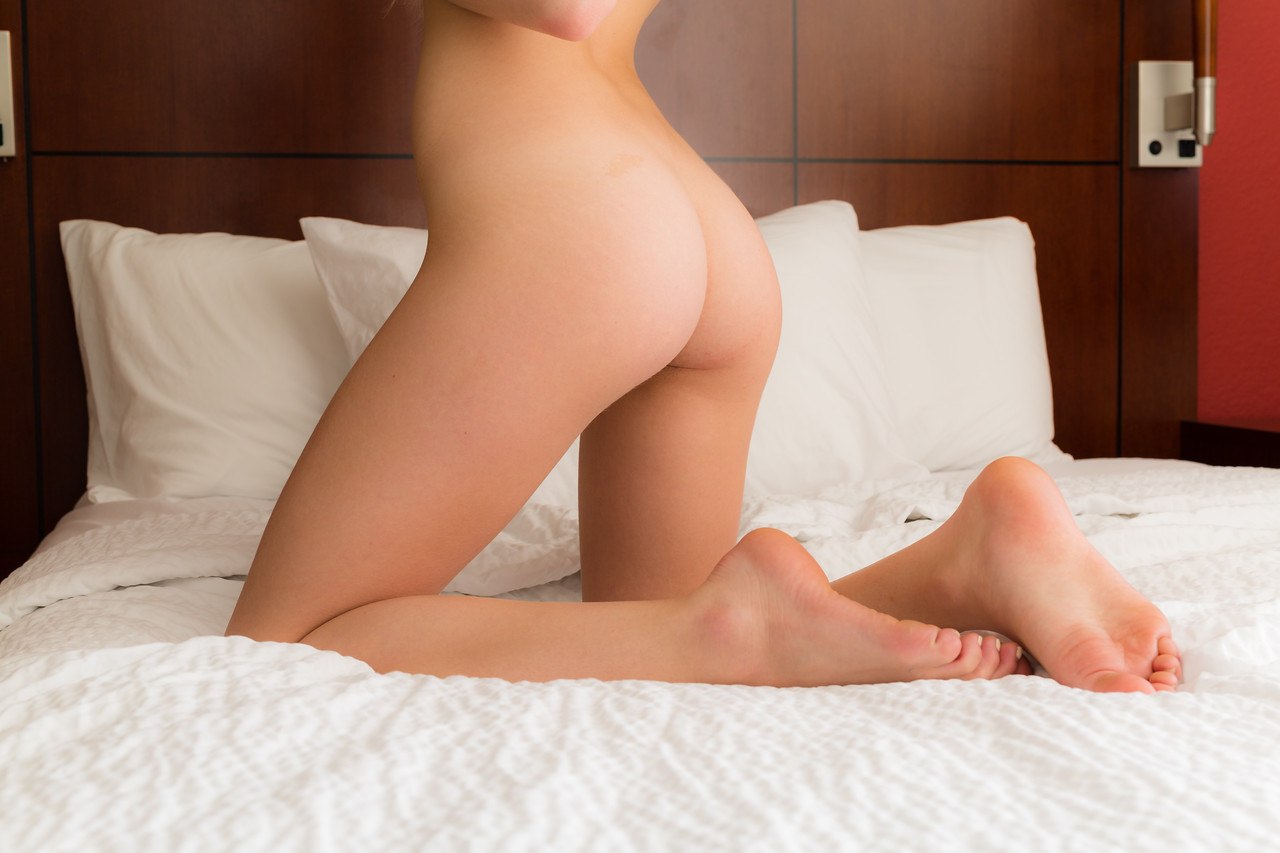 Blonde caucasian woman poses on a bed nude