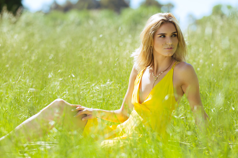 Attractive young blonde Caucasian woman in thin yellow sun dress posing outside in long grass