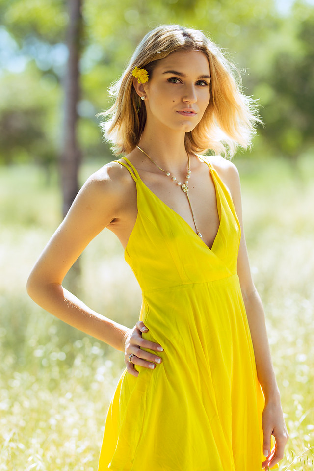 Attractive young blonde Caucasian woman in thin yellow sun dress with flowers in hair posing outside near grass and trees