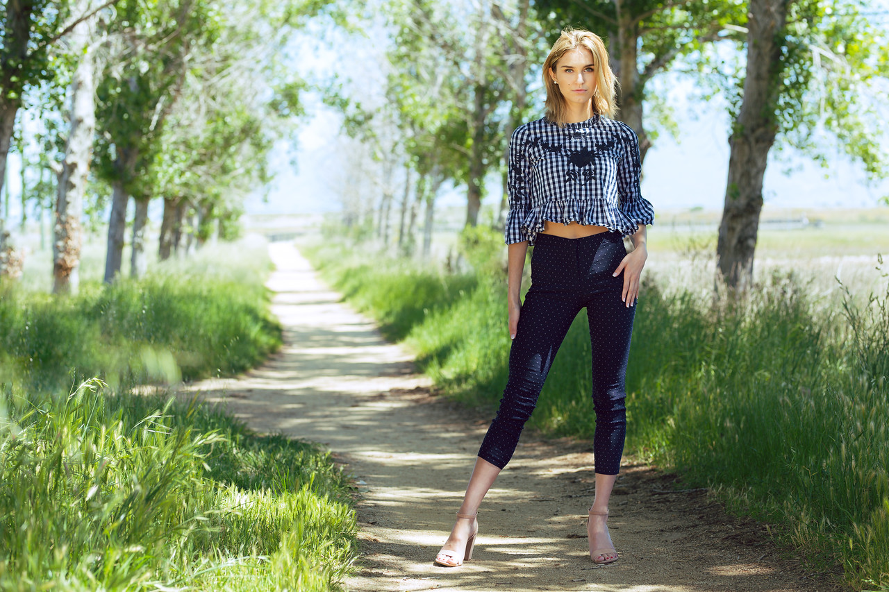 Attractive young blonde Caucasian woman in plaid top and denim posing outside on empty dirt road