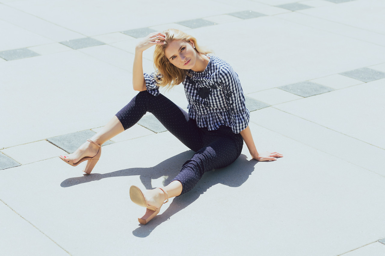 Attractive young blonde Caucasian woman in plaid top and denim posing outside