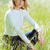 Attractive young blonde Caucasian woman in tight white top and denim posing outside in long grass