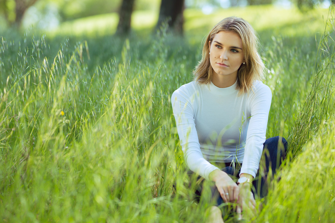Attractive young blonde Caucasian woman in tight white top and denim posing outside among long grass and trees