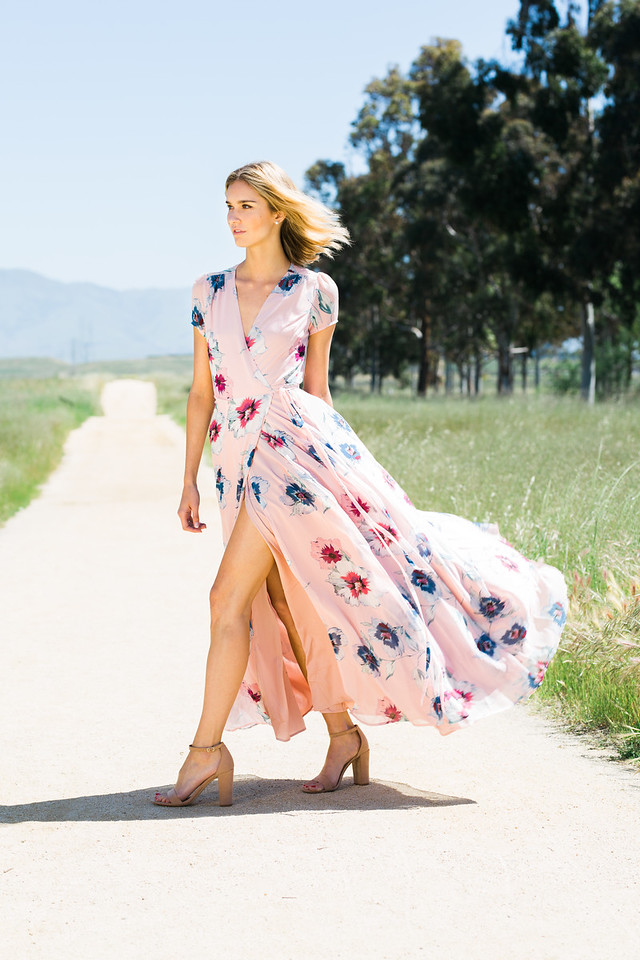 Attractive young blonde Caucasian woman in flowing pink floral print dress posing outside runway style on empty dirt road