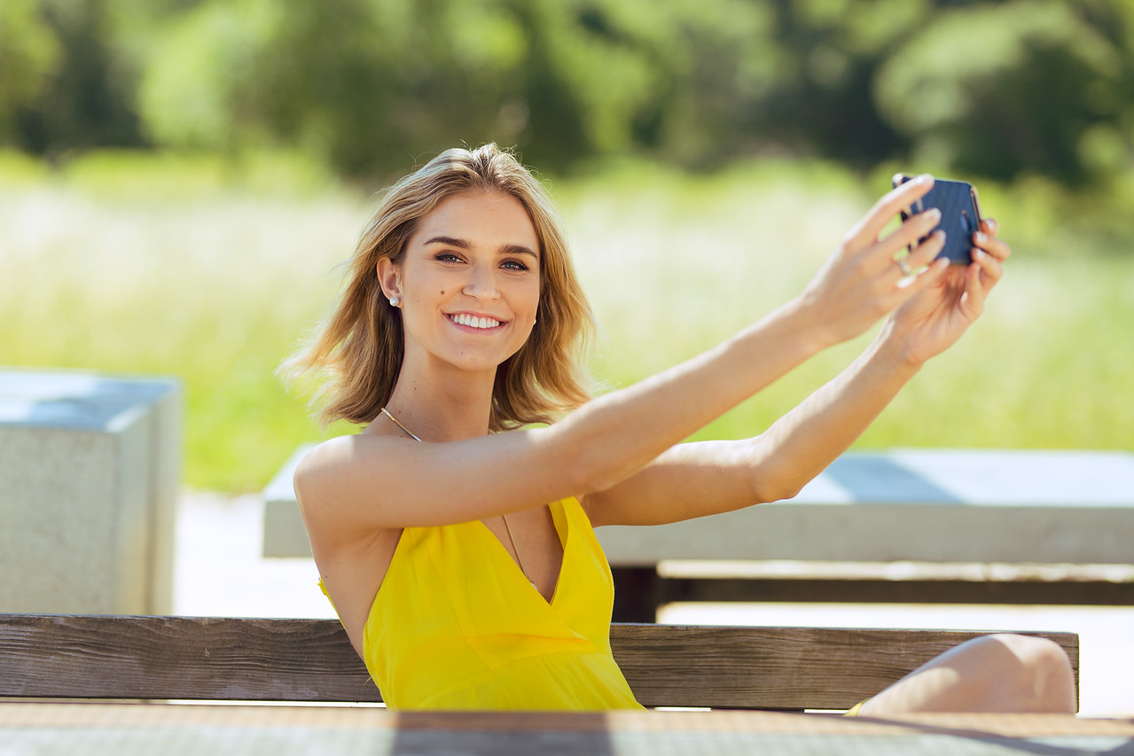 Attractive young blonde Caucasian woman in thin yellow sun dress using a large smartphone outdoors