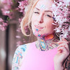 Tight portrait of blonde caucasian woman with tattoos near pink flowers