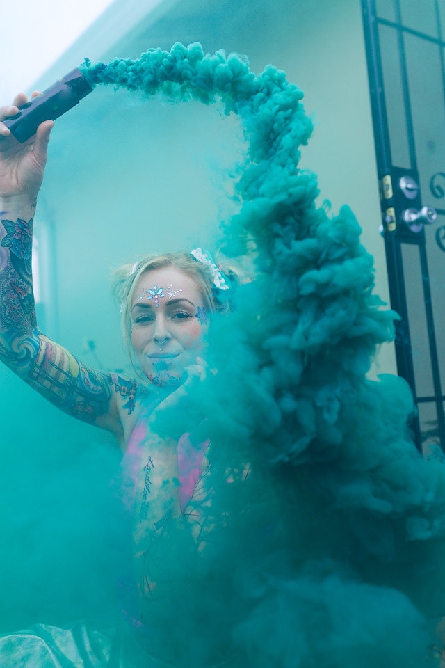 Wide portrait of blonde caucasian woman with tattoos using green smoke bomb in an urban location