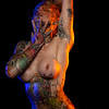 Muscled caucasian woman with tattoos and oiled skin poses under colored lights