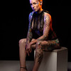 Muscled caucasian woman with tattoos and oiled skin wearing heels poses under colored lights on stool