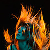 Alternative model with bangs and colored hair poses under teal and orange light wearing a fishnet top