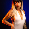 Alternative model with bangs and colored hair poses under blue and orange light wearing a white leotard