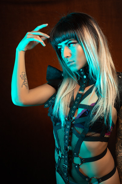 Alternative model with bangs and colored hair poses under blue light wearing a leather outfit