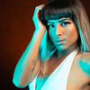 Alternative model with bangs and colored hair poses under blue light wearing a white leotard