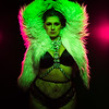 Curvy alternative model with colored hair and fur coat and fishnets under green and pink lighting