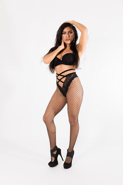 Young fit hispanic woman in black two piece, fishnets, and high heels poses on a white background