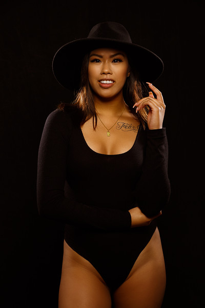 Fit young asian woman in black one piece and necklace poses against black background