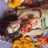 Young caucasian woman lies in a pile of flowers against a blue background. Sheer white dress
