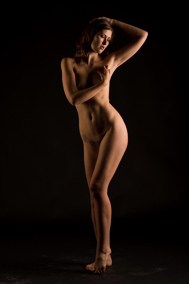 Tall young caucasian woman poses in the nude against a pure black background