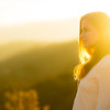 Close up of young mixed race woman in white dress standing above a valley at sunrise
