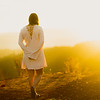 Young mixed race woman in white dress standing above a valley at sunrise